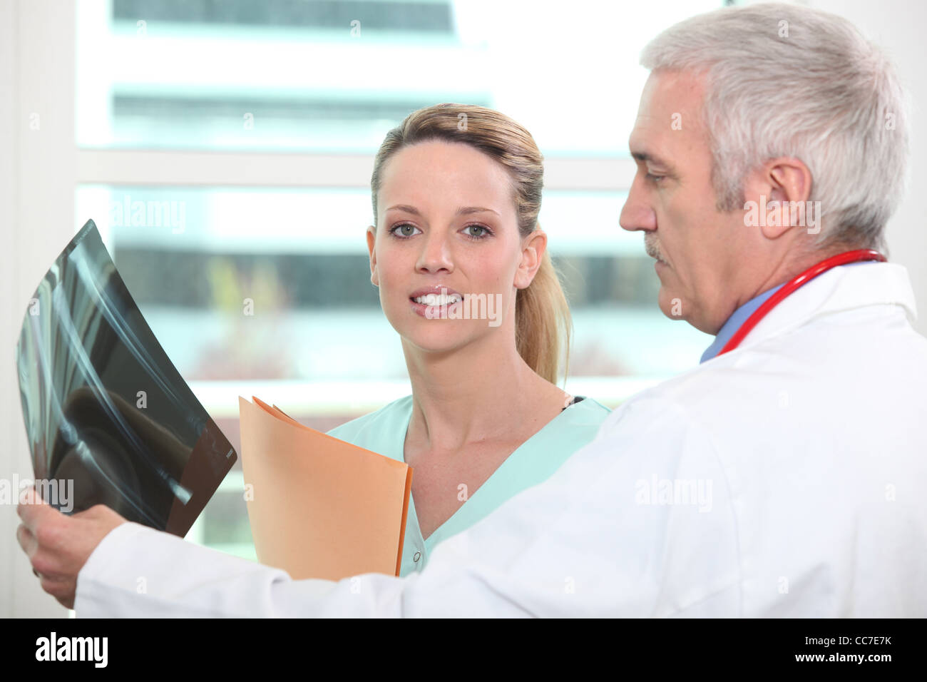 Doctor and colleague examining x-ray - Stock Image