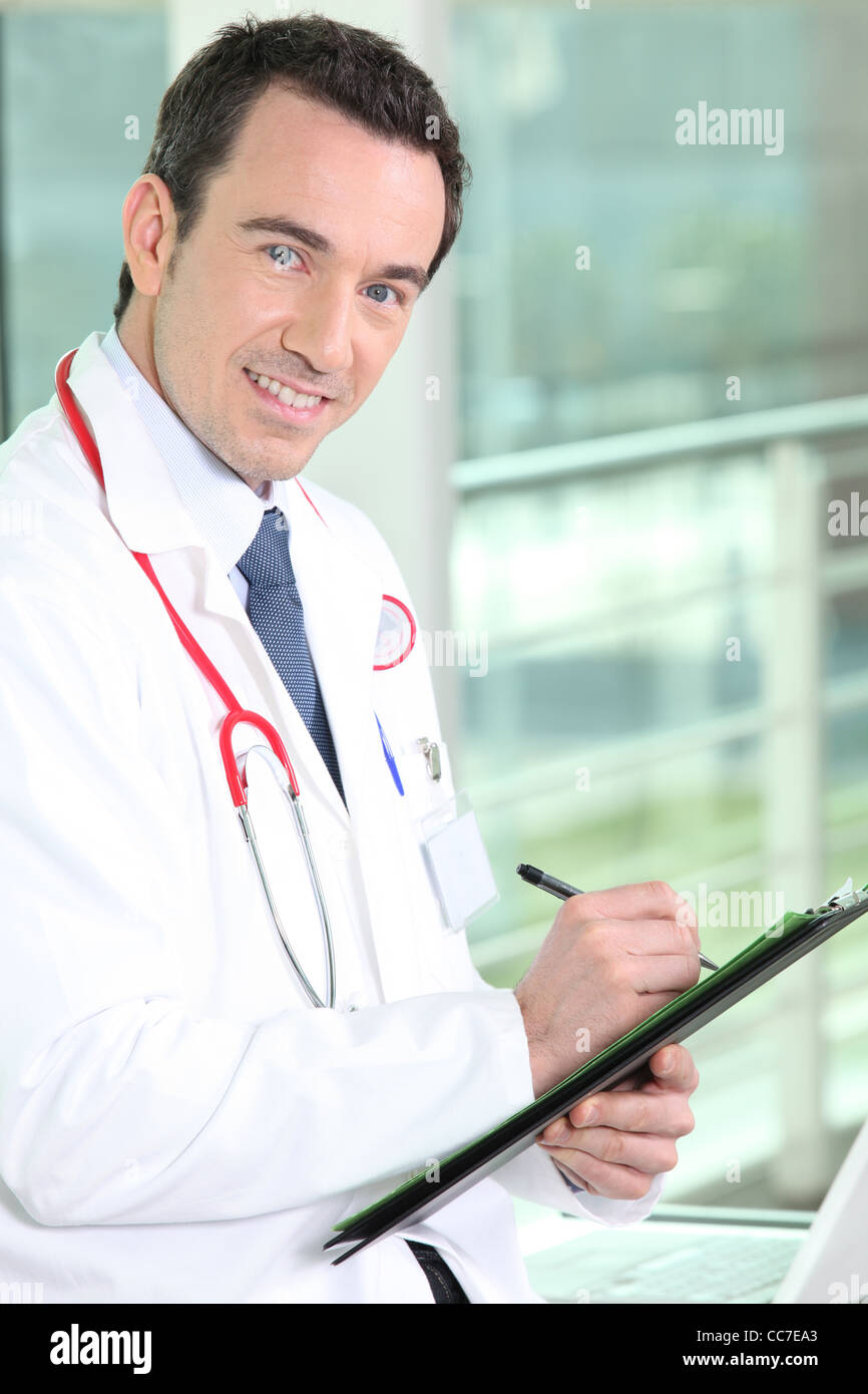 Smiling practitioner writing on medical record - Stock Image