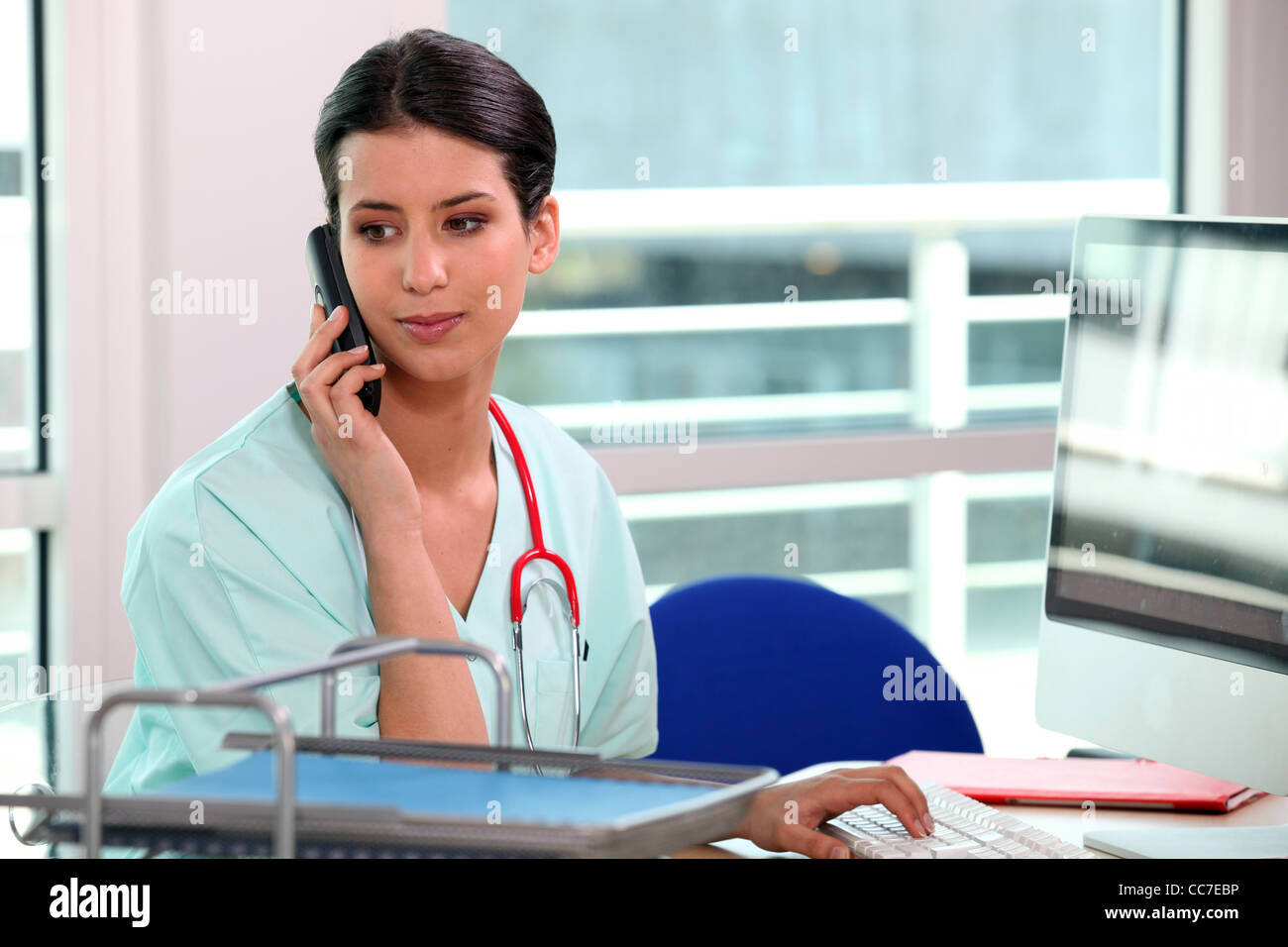 young nurse at phone behind her computer - Stock Image