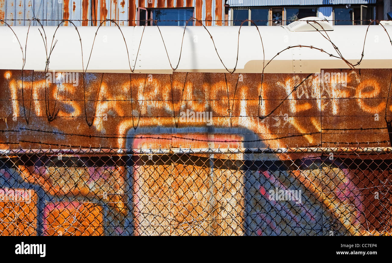 it's a rough life graffiti painted on rusted metal wall - Stock Image