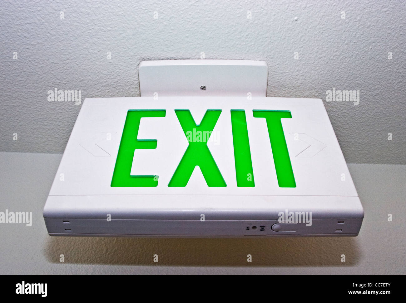 exit sign mounted on ceiling in hallway - Stock Image
