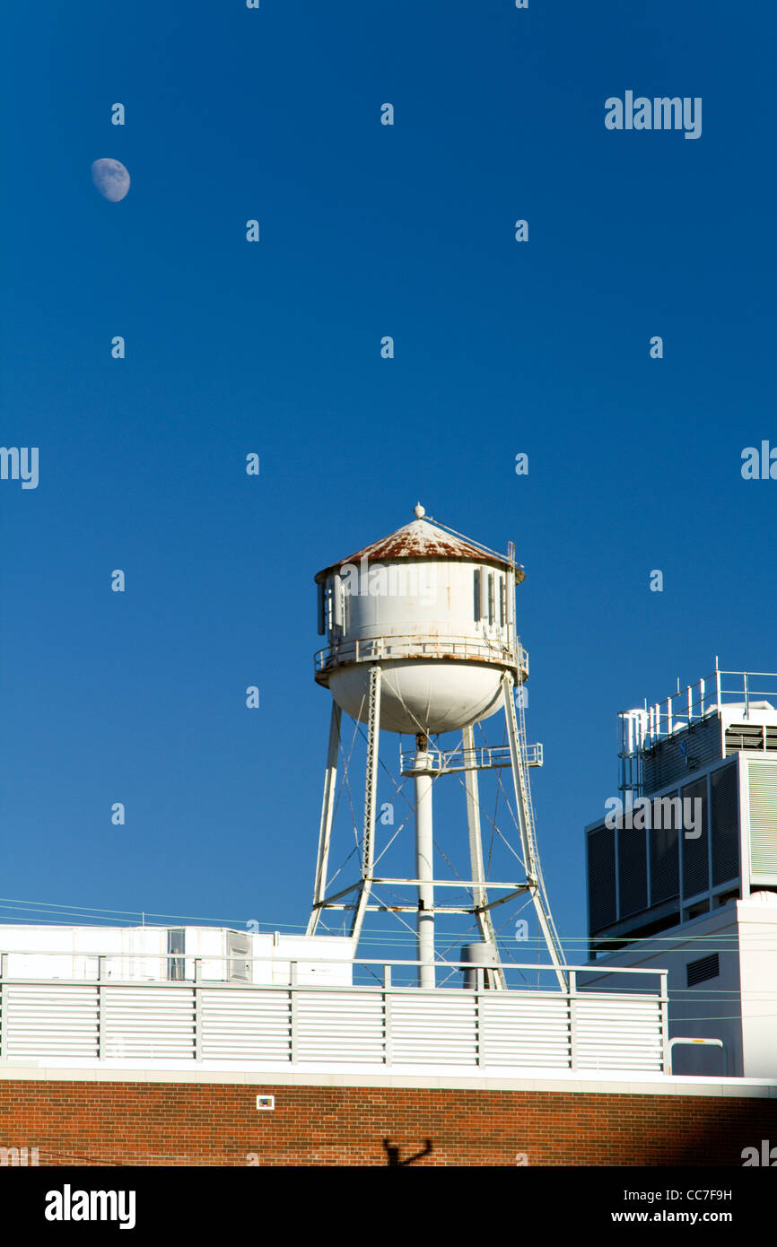 Rooftop water tower with moon - Stock Image