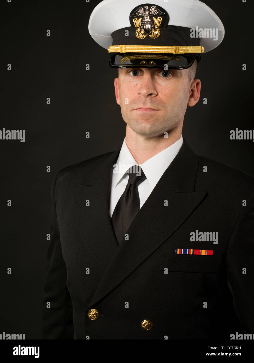 United States Navy Officer in Service Dress Blues Uniform with Combination Cover ( hat ) - Stock Image