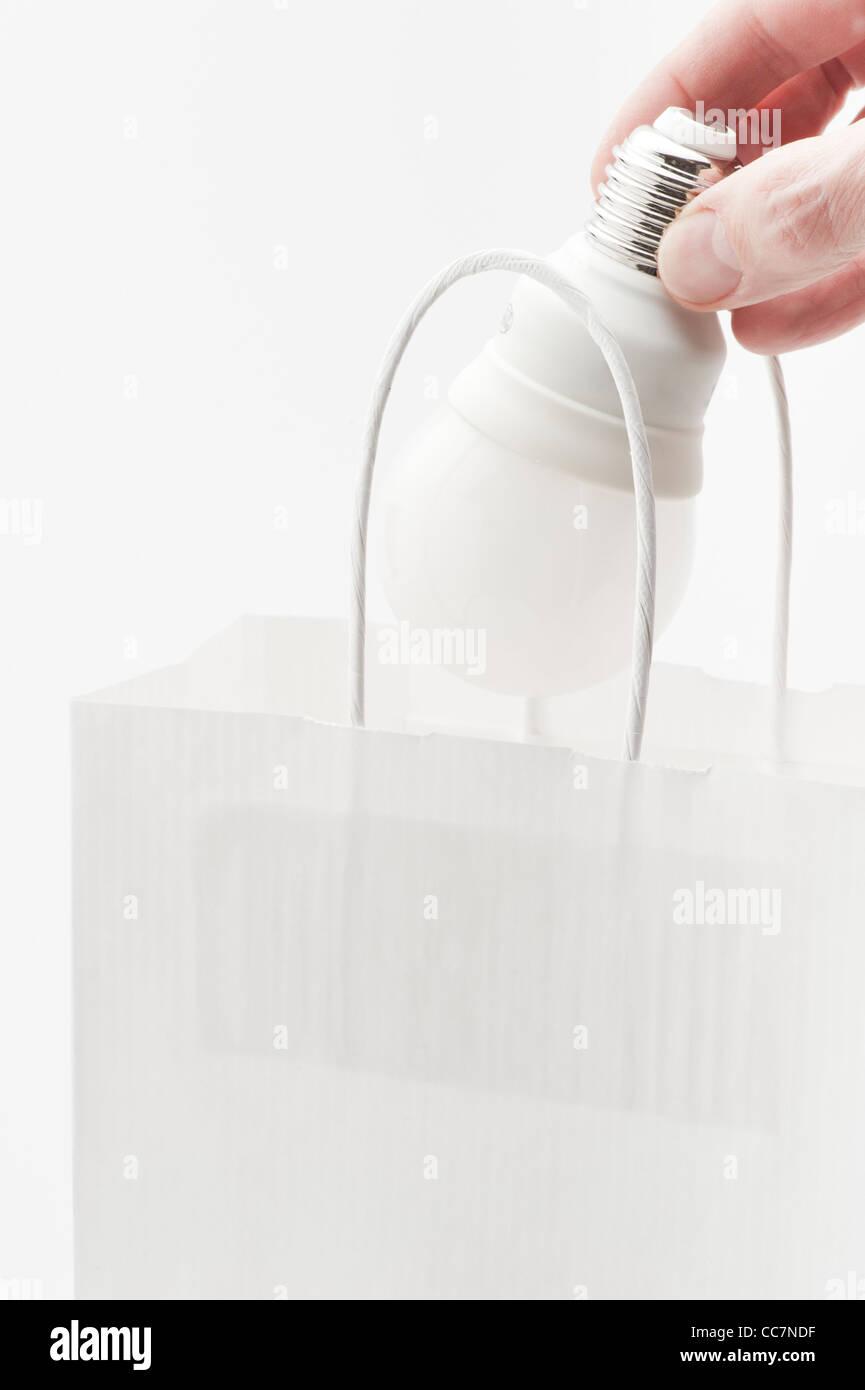 Hand placing energy efficient lightbulb in paper bag - Stock Image