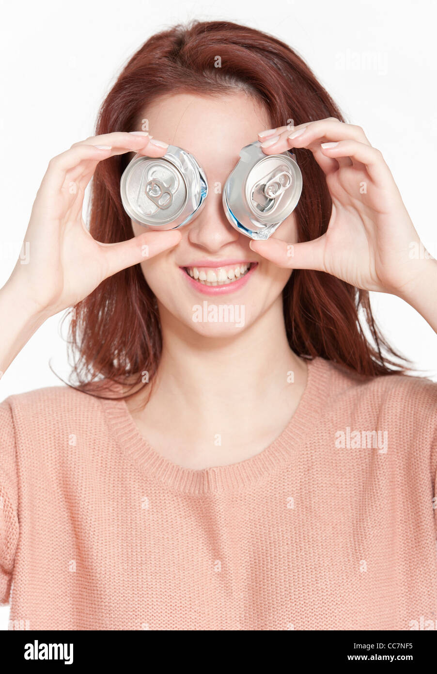 Young woman holding two crushed drink cans in front of face - Stock Image