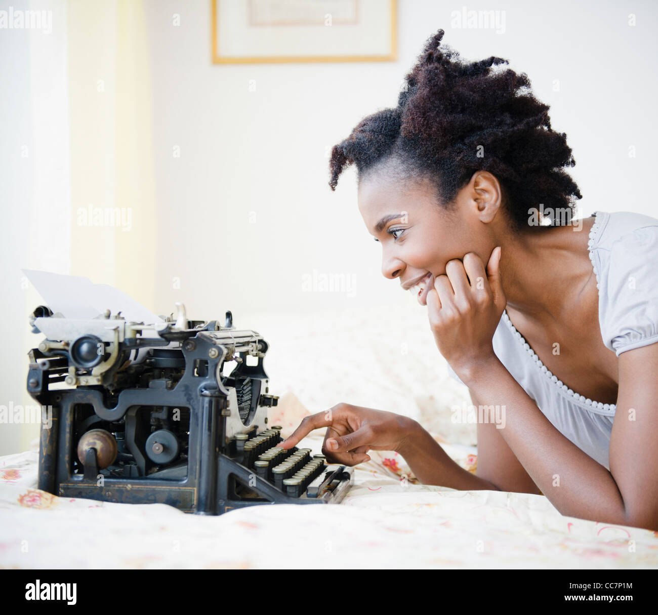 Black woman using old-fashioned typewriter Stock Photo