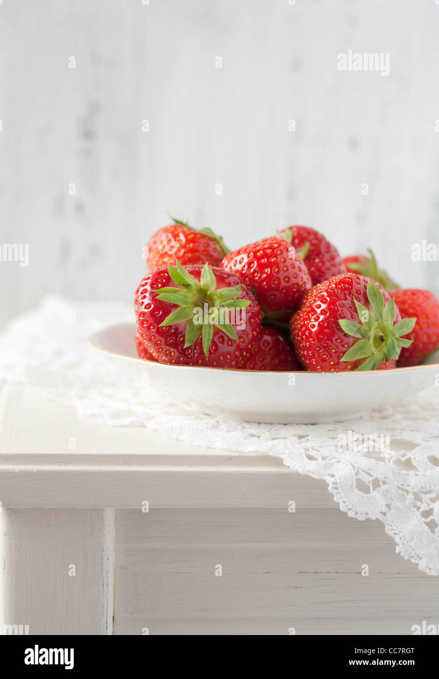 Strawberries on a white table with a crochet mat - Stock Image