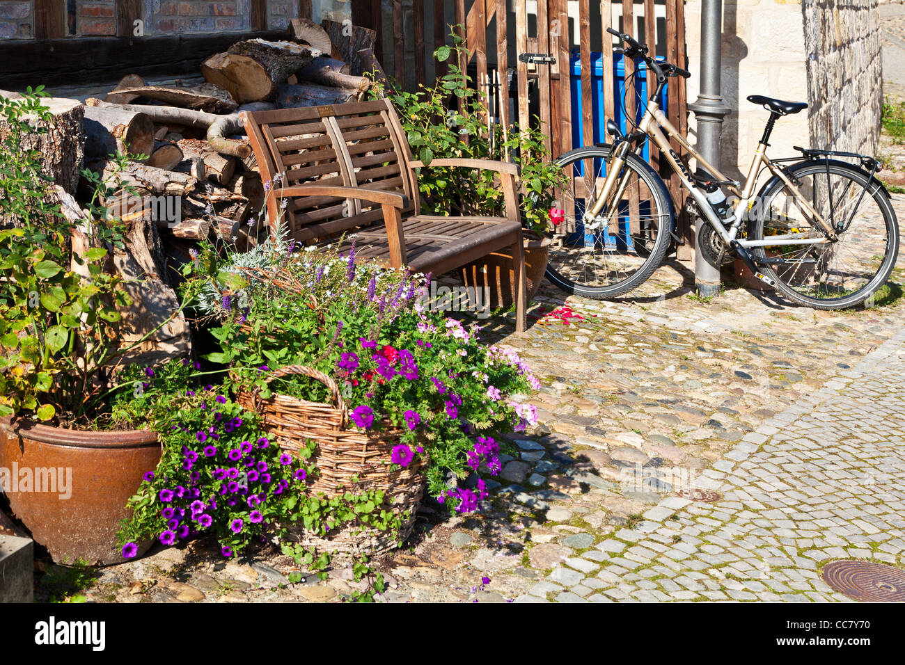 Bicycle and wooden seat outside a house in the UNESCO World Heritage town of Quedlinburg, Germany. - Stock Image