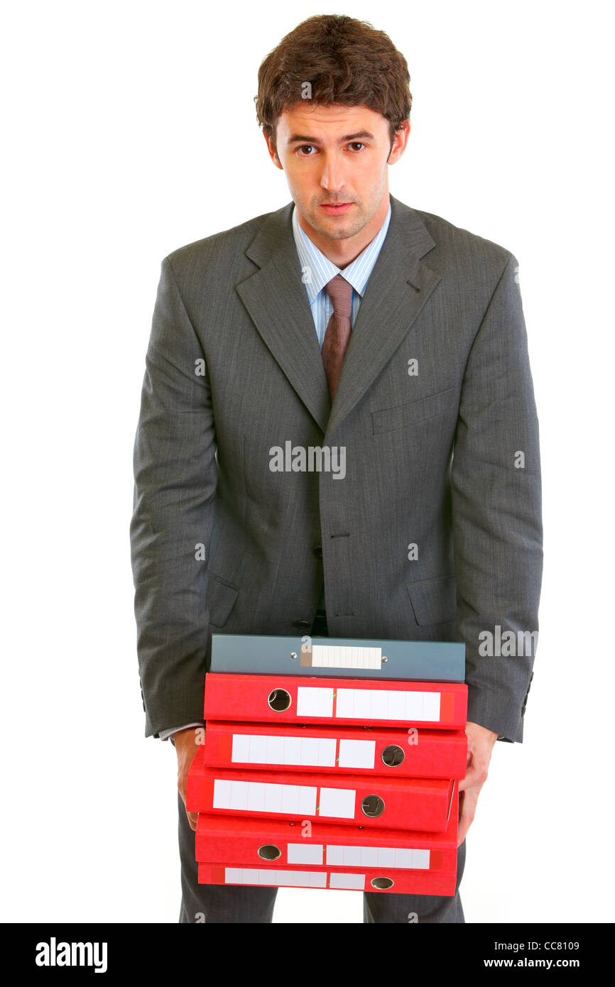 Stressful young businessman holding in hands heavy pile of folders isolated on white - Stock Image