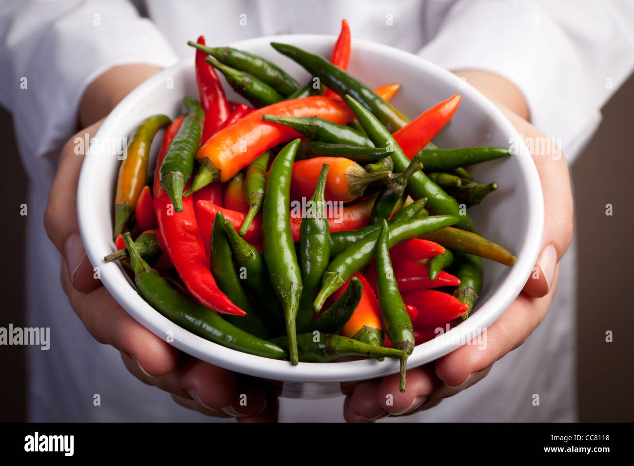 Chef holding a bowl mixed hot chillies - Stock Image