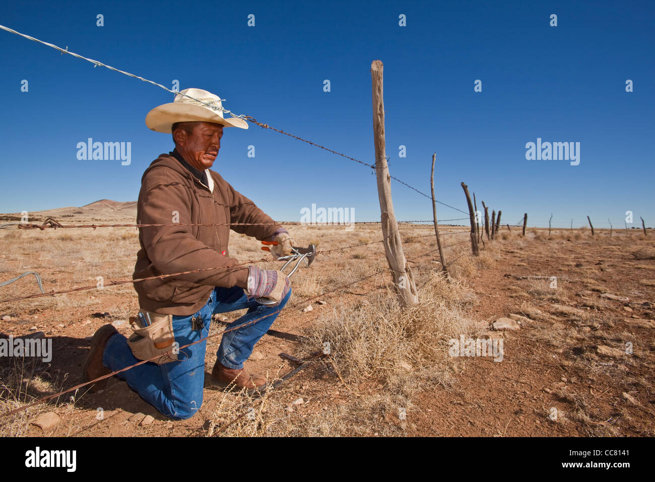 Navajo fence worker, repairing barbed wire fence on the CO Bar Ranch, north of Flagstaff, Arizona, USA - Stock Image