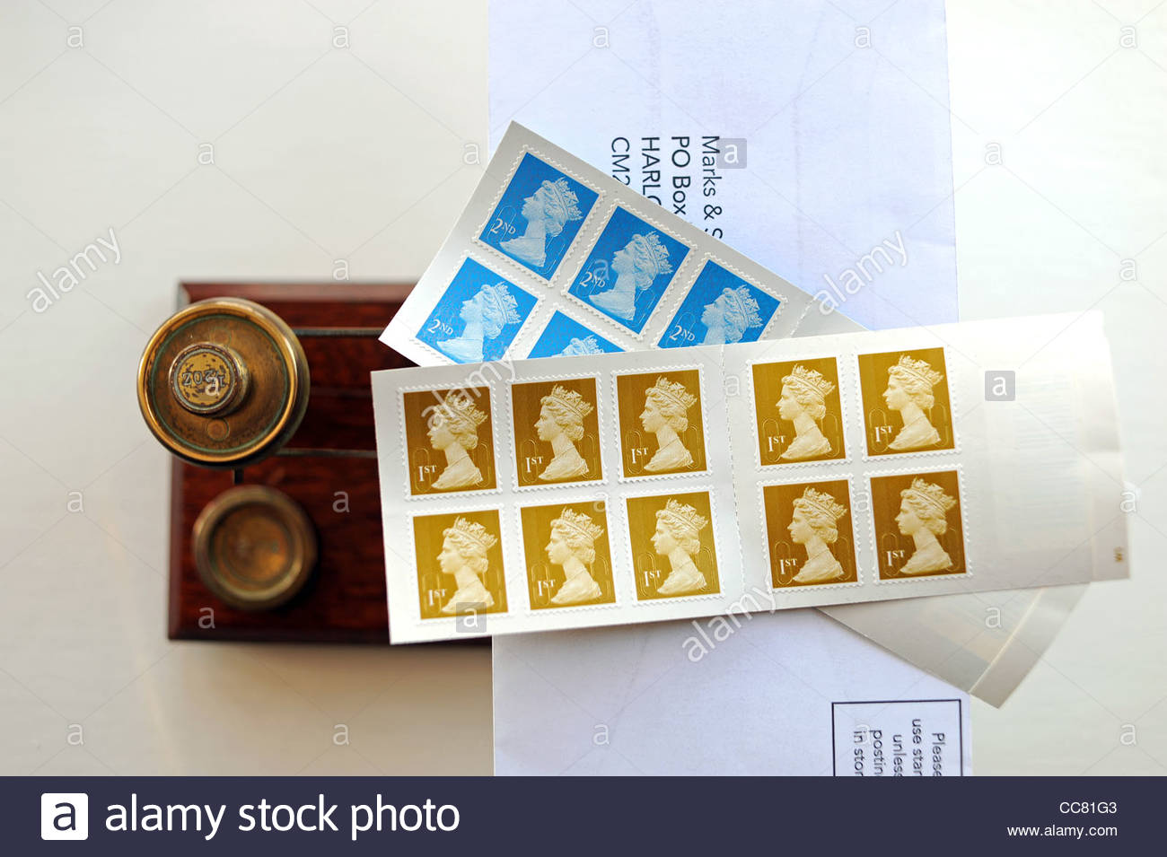 British First 1st class postage stamps UK on a letter sitting on old fashioned post office scales UK
