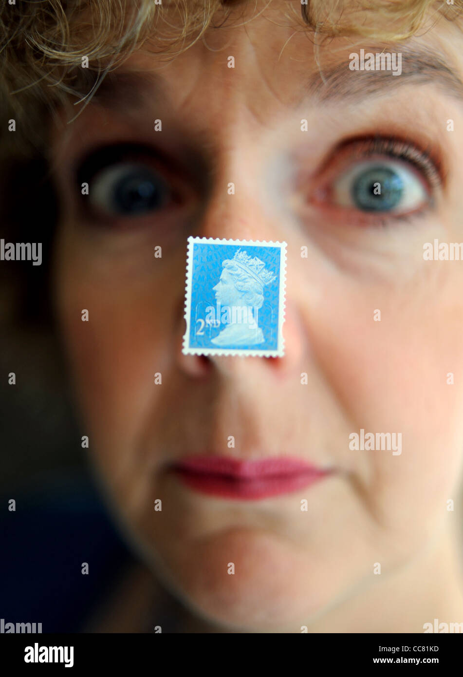 Middle aged woman close up face with a British second 2nd class postage stamp stuck to nose model Stock Photo