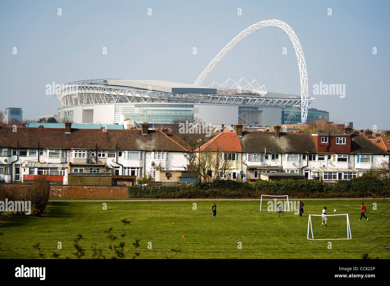 Wembley stadium seen from Brent River Park in the London borough of Brent with boys playing football in front and - Stock Image