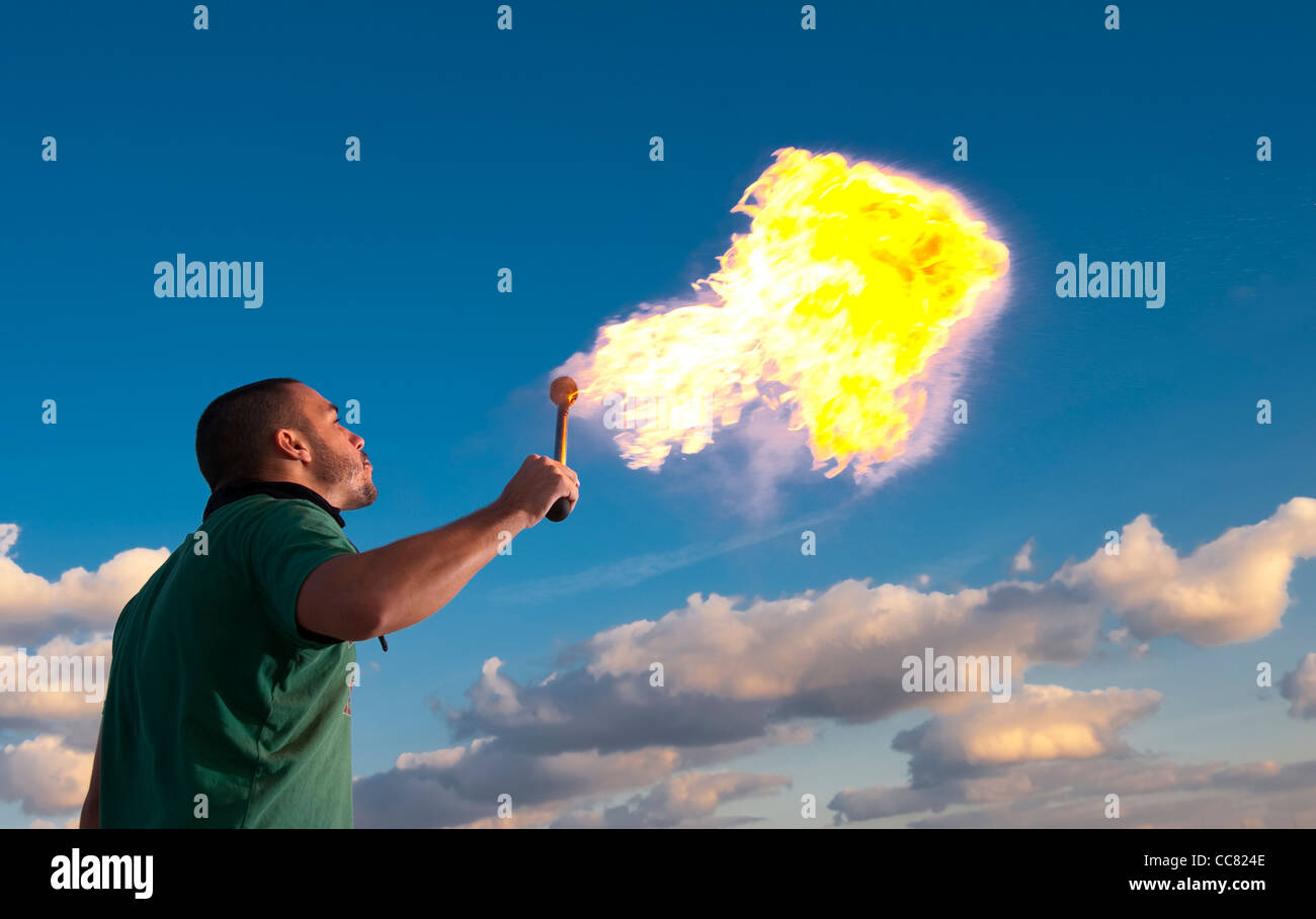 Male fire eater performing at dusk. - Stock Image