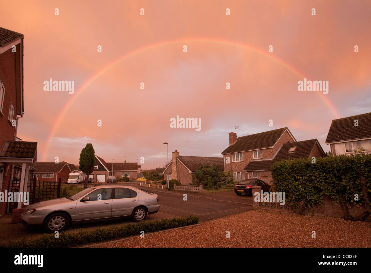 Genuine red orange sky (no filters) with complete rainbow arc created by freak, weird, unusual phenomenon weather - Stock Image