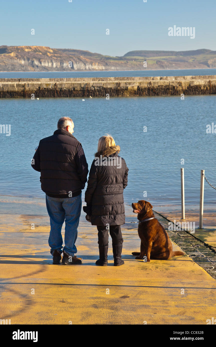 Two pet owners and their dog at the harbour in Lyme Regis on a winter morning, Dorset, England, UK - Stock Image