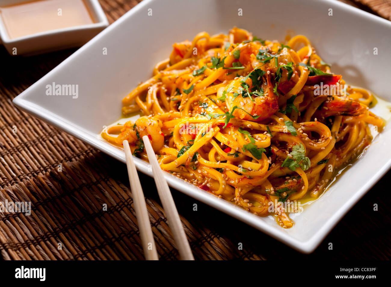 Chinese noodles with shrimps on a bamboo table - Stock Image