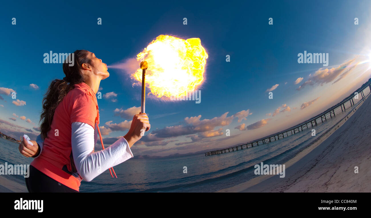 Female fire breather performing on Alcudia beach at dusk. - Stock Image
