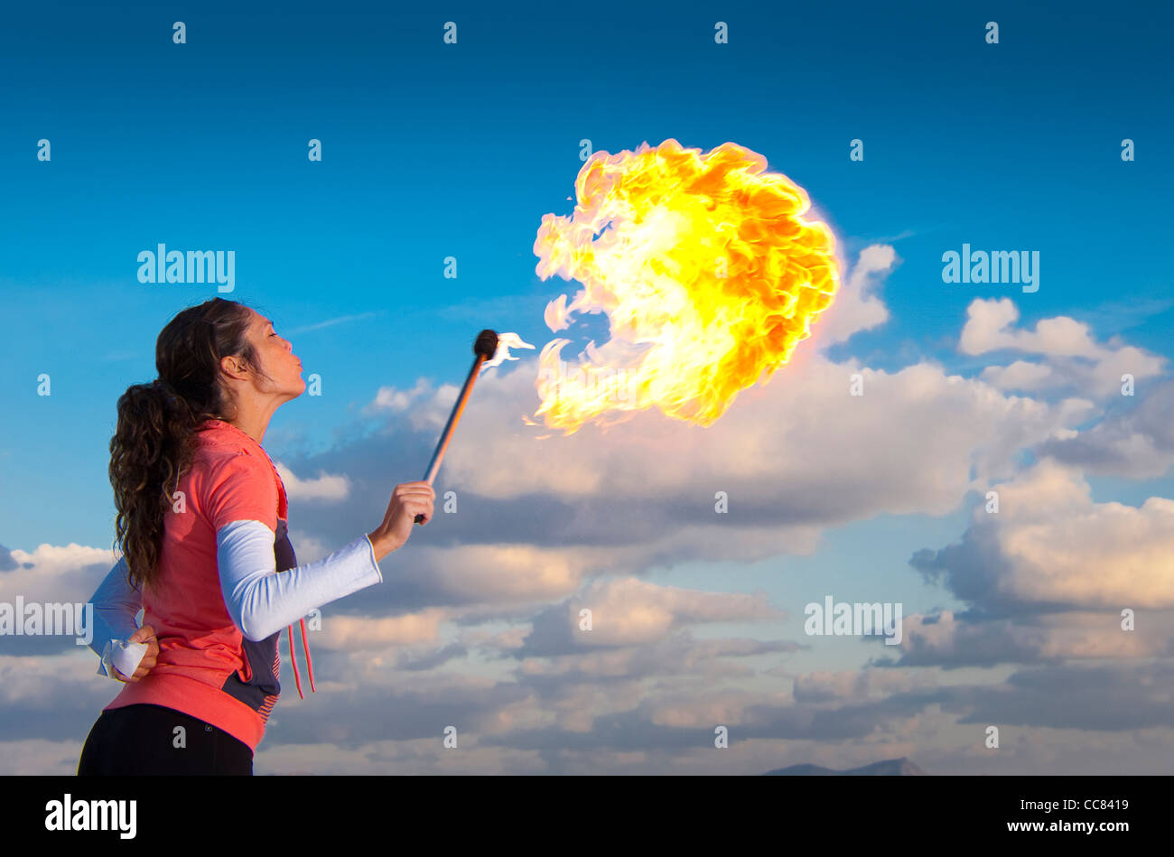 Female fire breather performing at dusk. - Stock Image