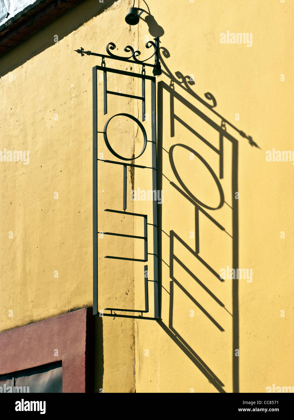 reverse read becomes right read in shadow cast by ornamental metal openwork hotel sign on ochre plaster wall Oaxaca - Stock Image