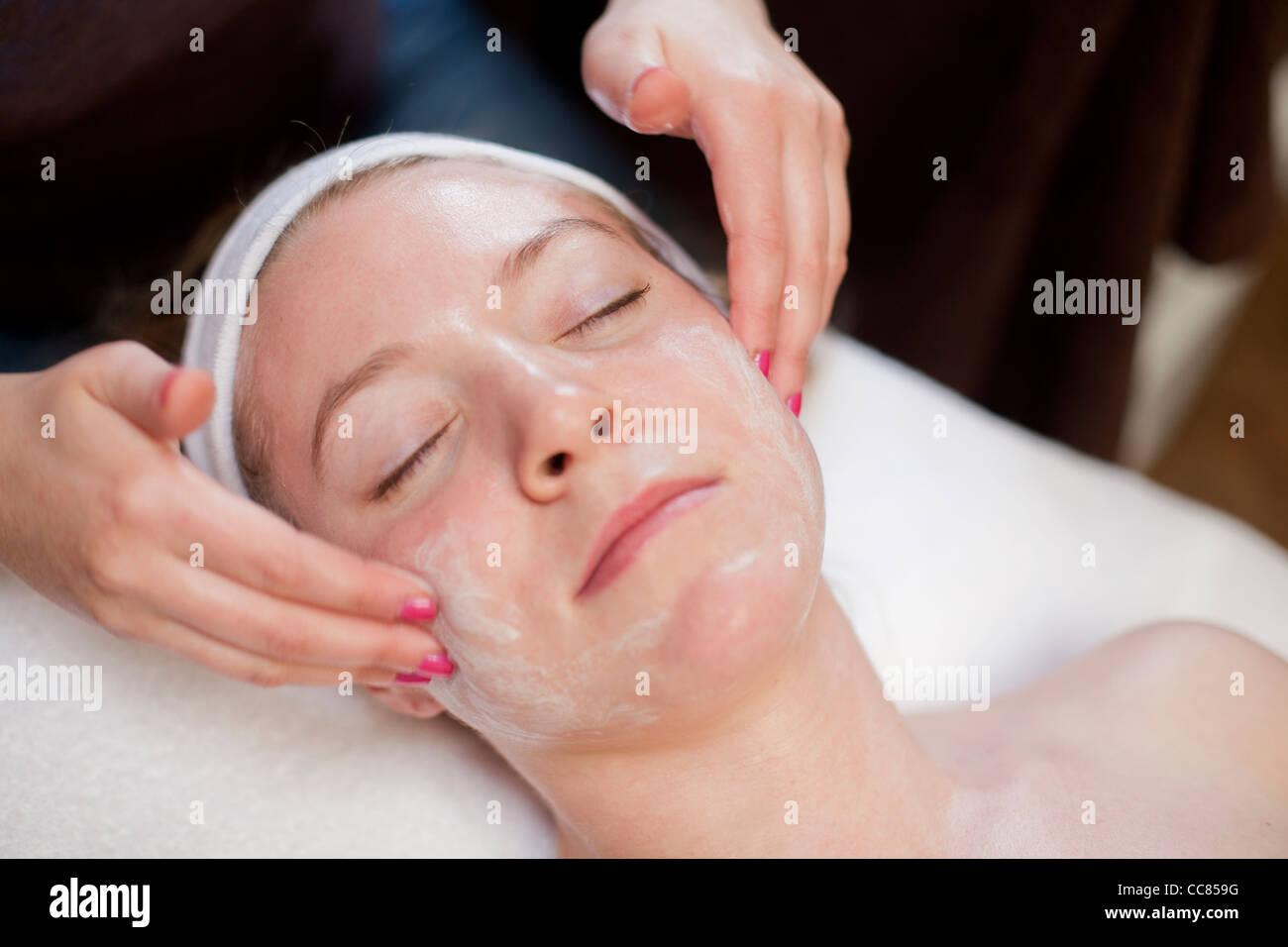 Young woman receiving a facial massage. - Stock Image