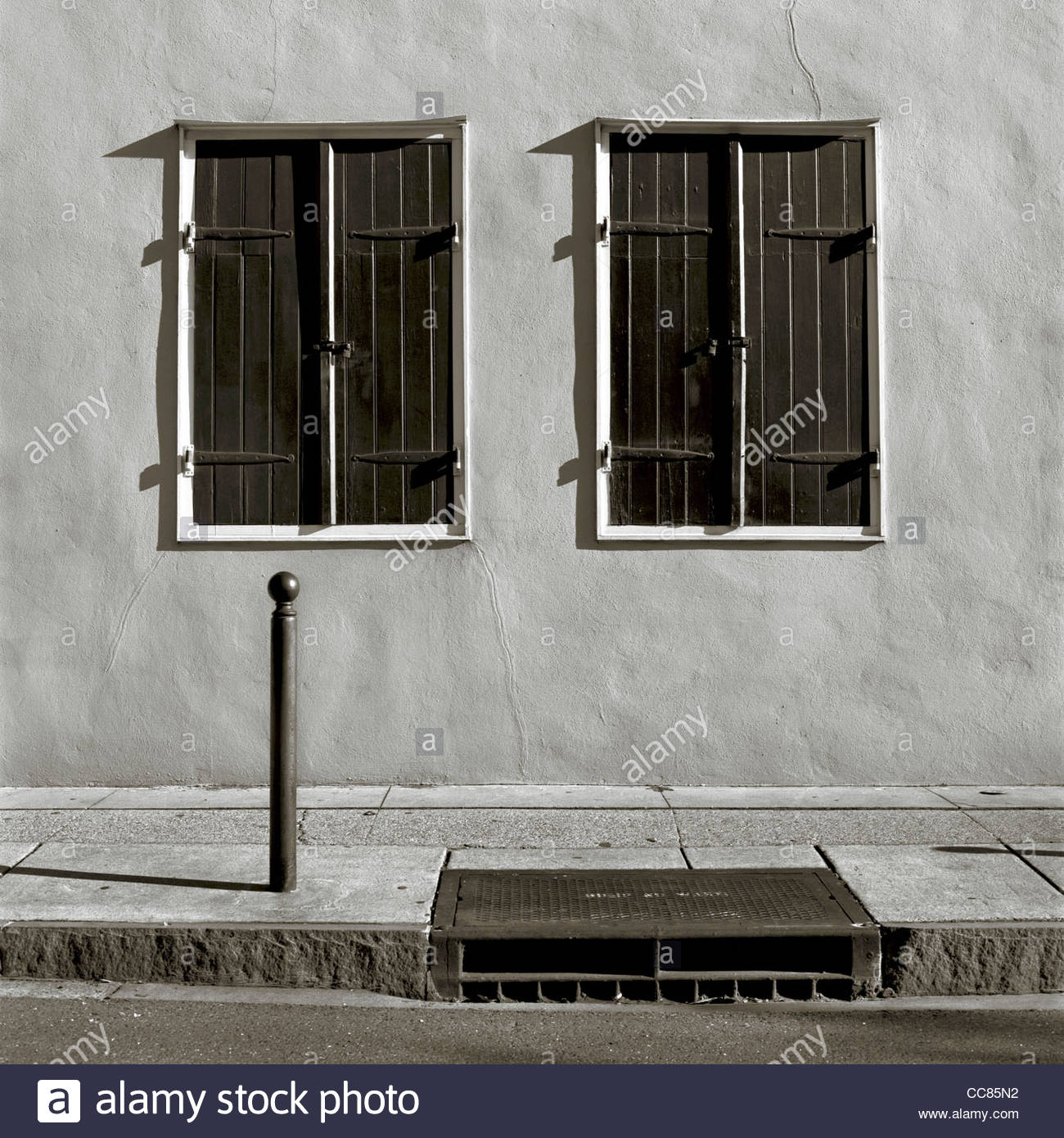 Two shuttered windows on a stucco wall, French Quarter, New Orleans, Louisiana, United States - Stock Image