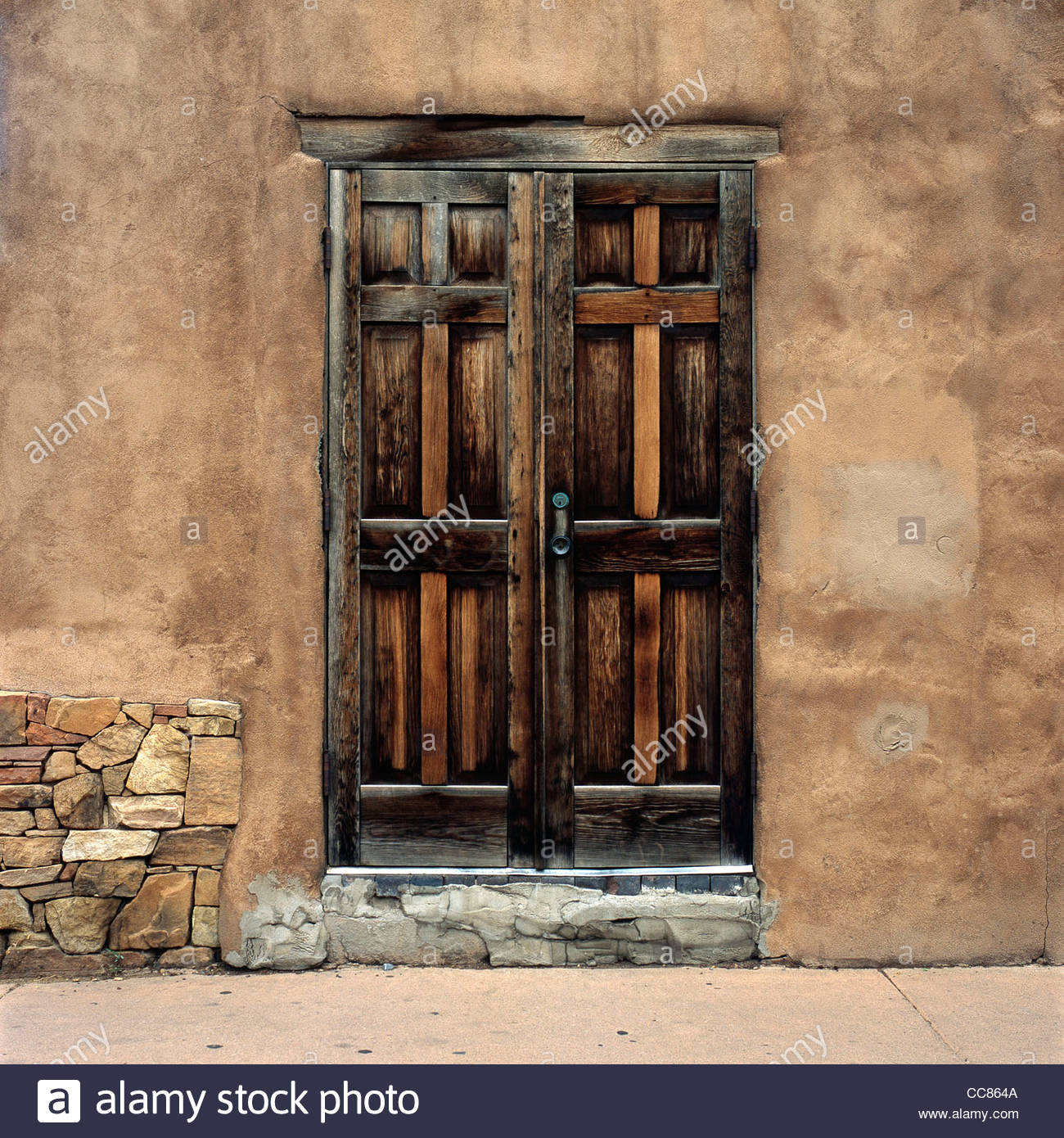 Wooden door on an adobe building, Santa Fe, New Mexico, United States - Stock Image