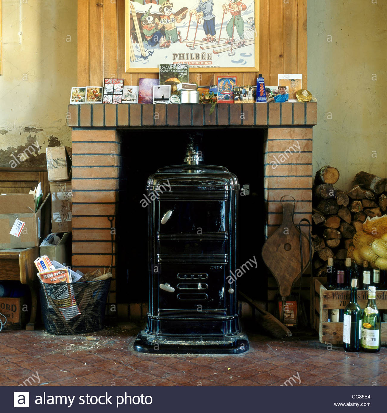 A wood-burning stove for heating in a fireplace in a rural country home, Limousin, France - Stock Image