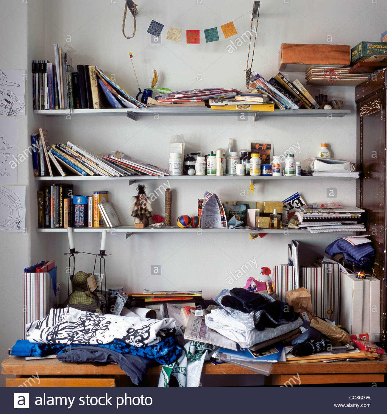 Shelves in a messy bedroom filled with books, vitamins, clothes, and photos - Stock Image