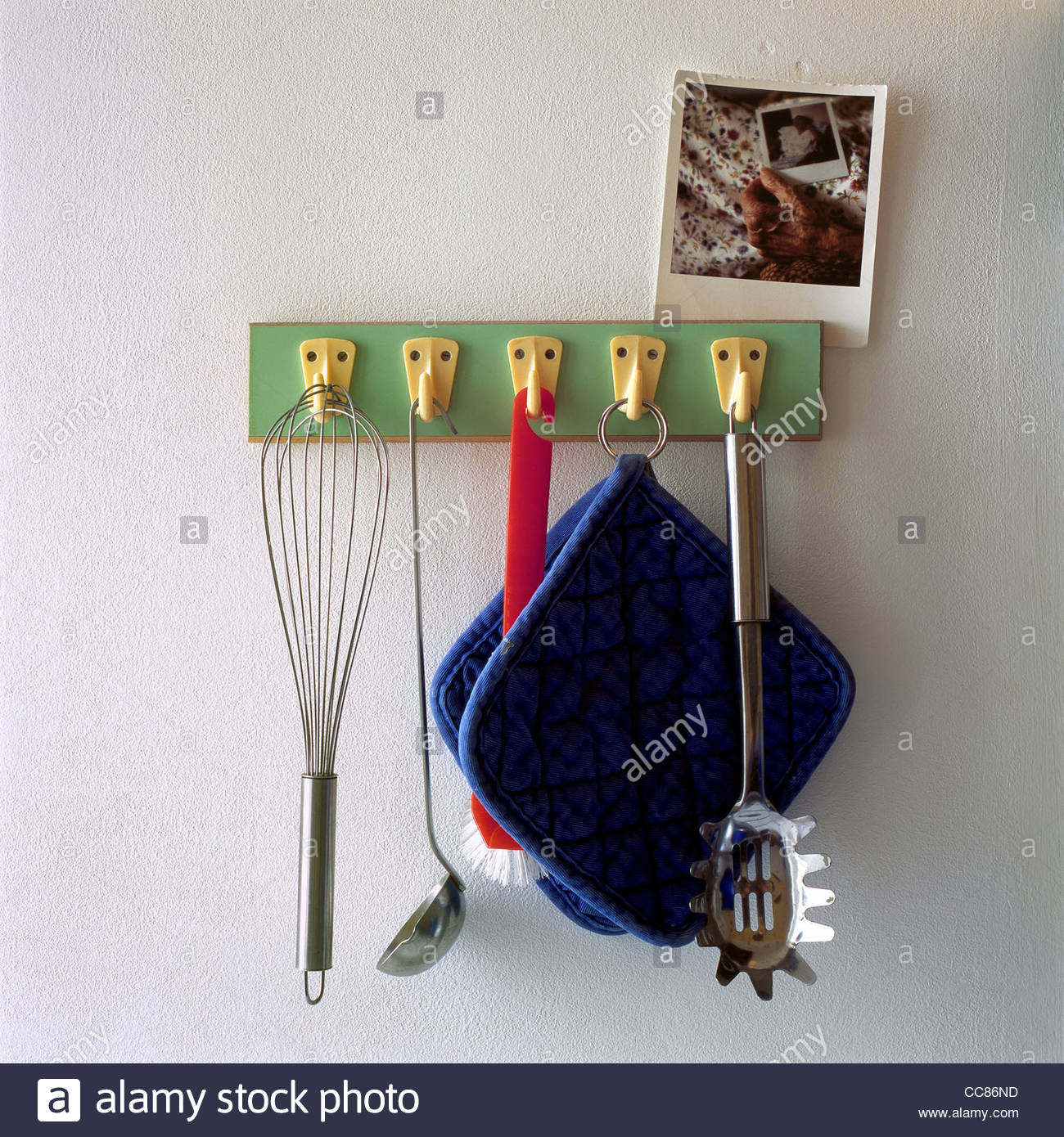 Kitchen utensils hanging on hooks on the wall - Stock Image