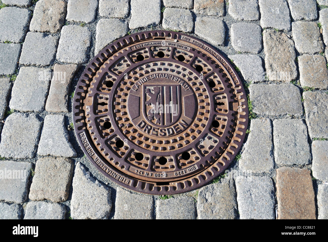 Cast-iron manhole cover with coat of arms of the city of Dresden. - Stock Image