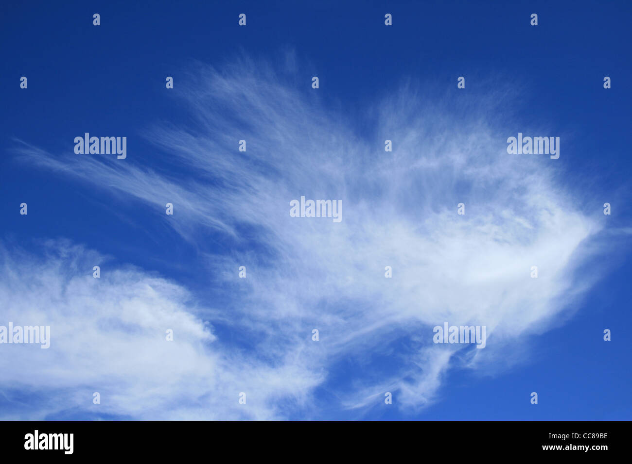 horizontal image of blue sky with wispy white cirrus clouds - Stock Image