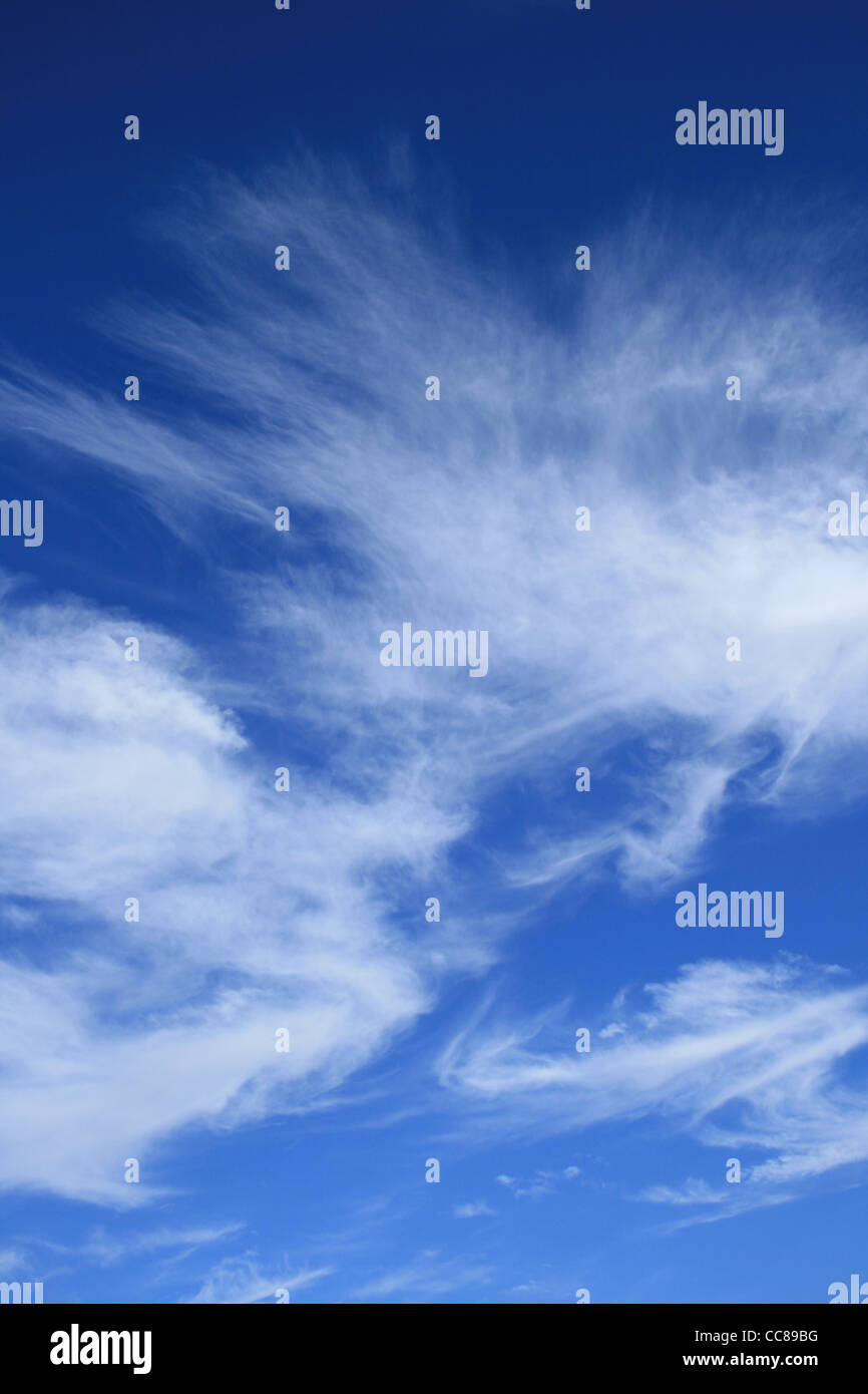 vertical image of blue sky with wispy white cirrus clouds - Stock Image