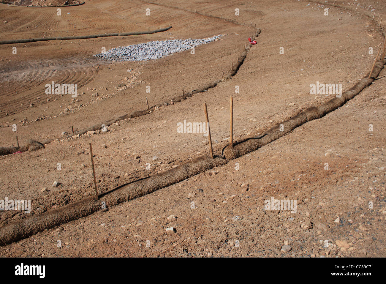 straw wattle erosion control structure protects soil and runoff at graded construction site - Stock Image