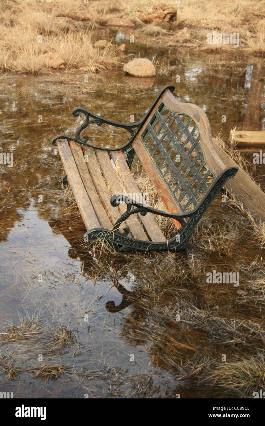 An Old Wood And Metal Park Bench Is Sinking Into A Large Puddle