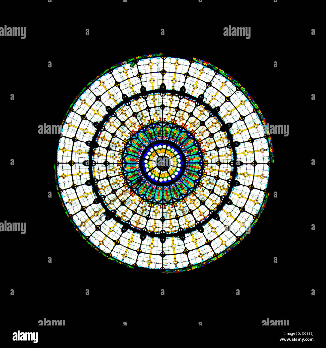 A colourful round stained glass window. - Stock Image