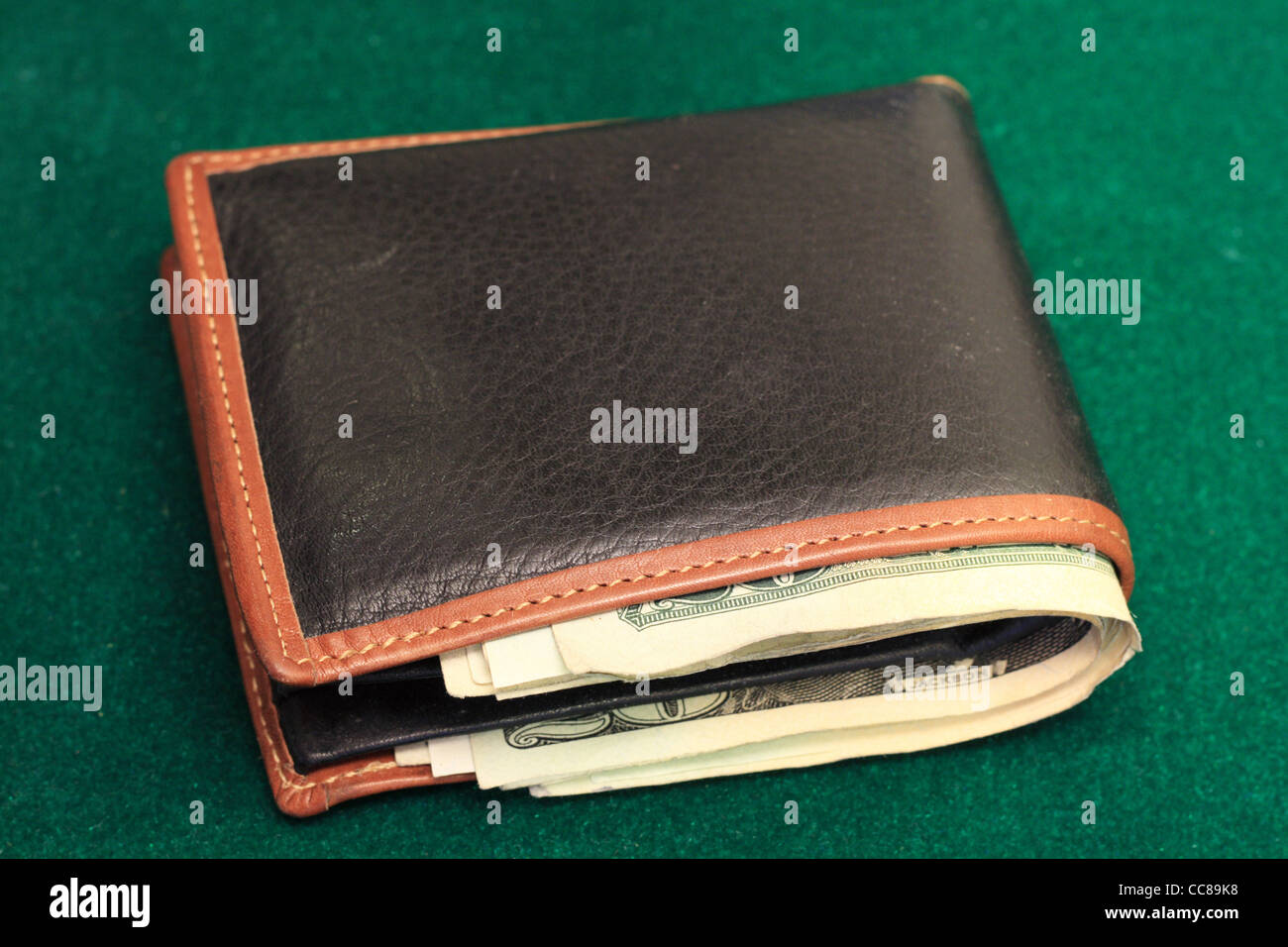 a leather wallet filled with US bills on a green felt background - Stock Image