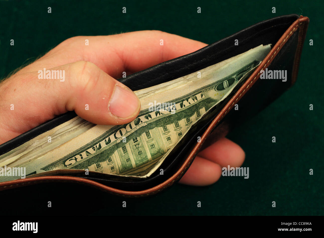 a man's hand holds a leather wallet filled with US bills open on a green background - Stock Image
