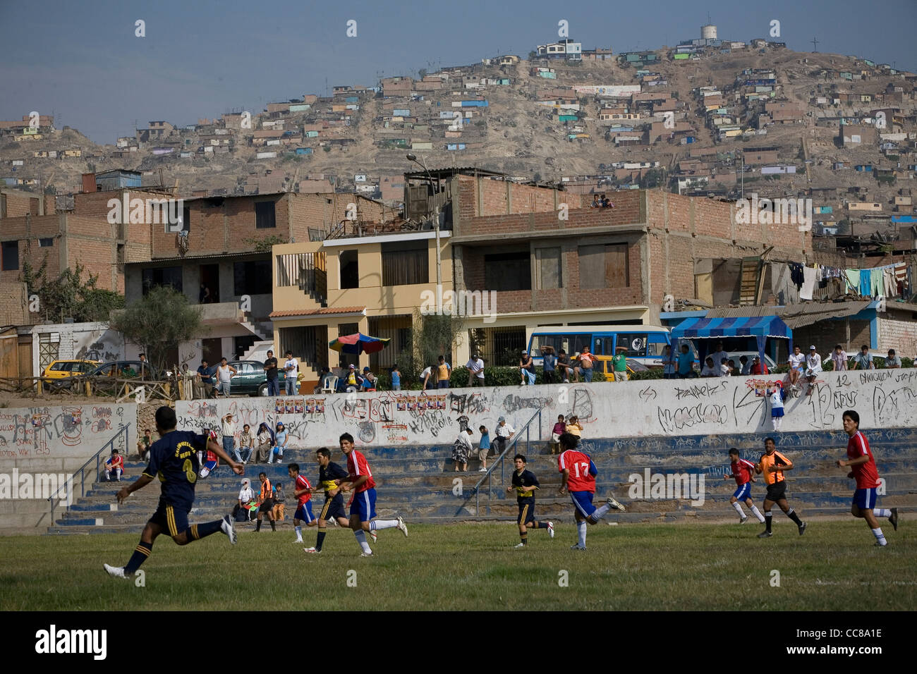 A football team competes on the pitch in Lima, Peru, South America. - Stock Image