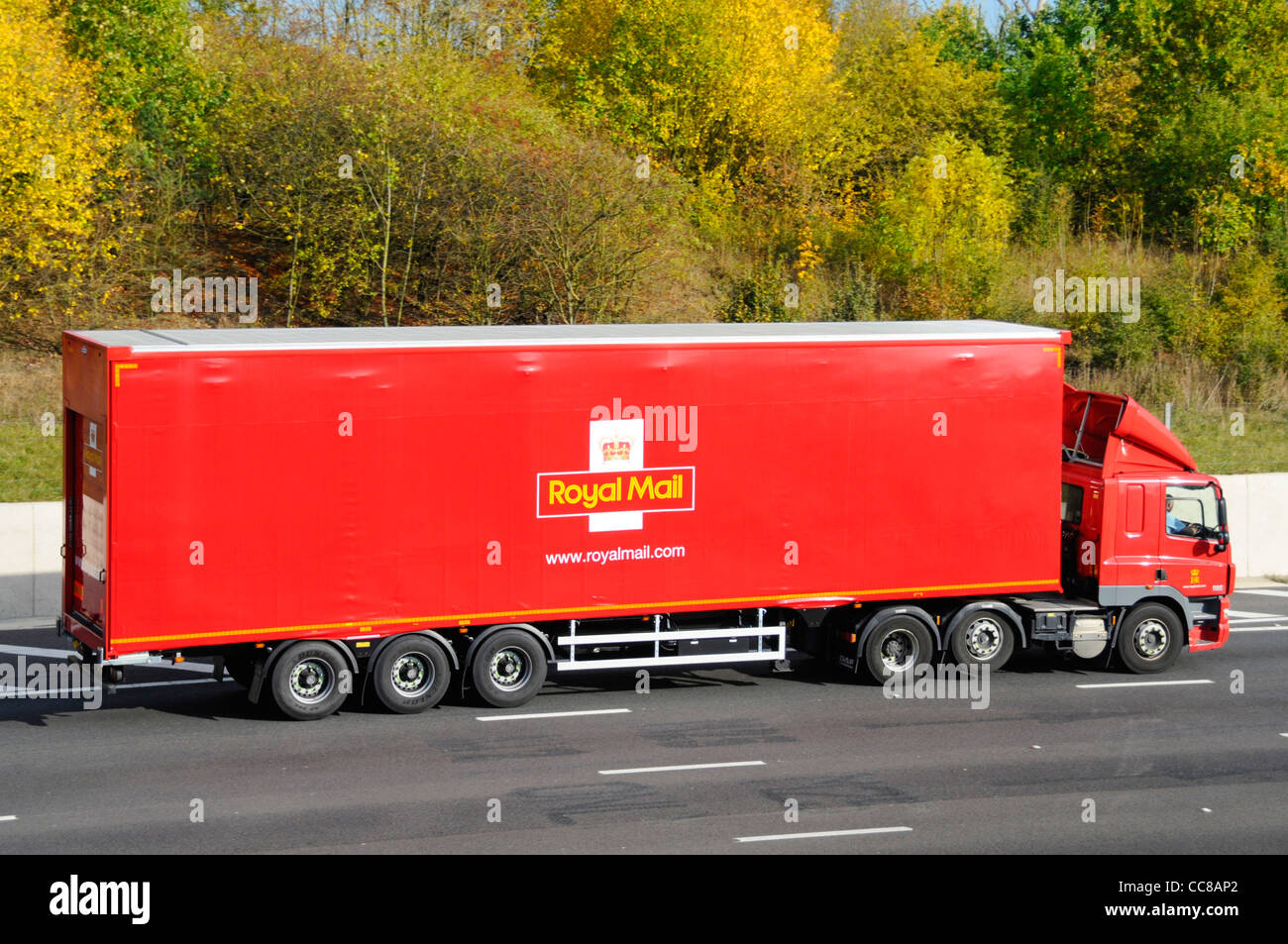 Side view of red Royal Mail logistics hgv distribution lorry truck juggernaut and articulated trailer driving along - Stock Image