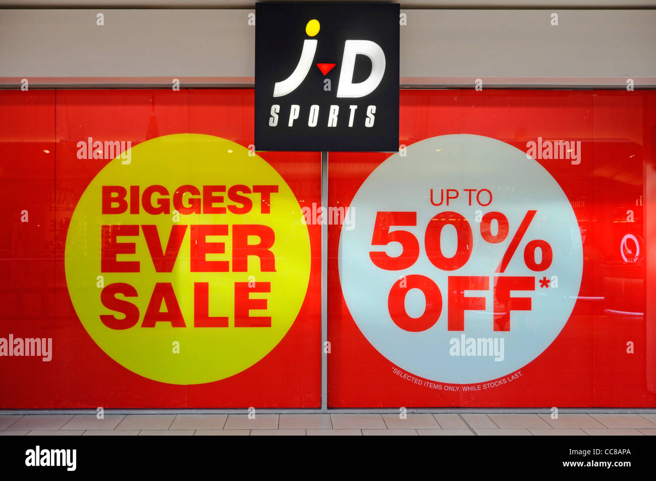 JD Sports shop front store window covered in large sign up to 50% discount  poster d326c97b5