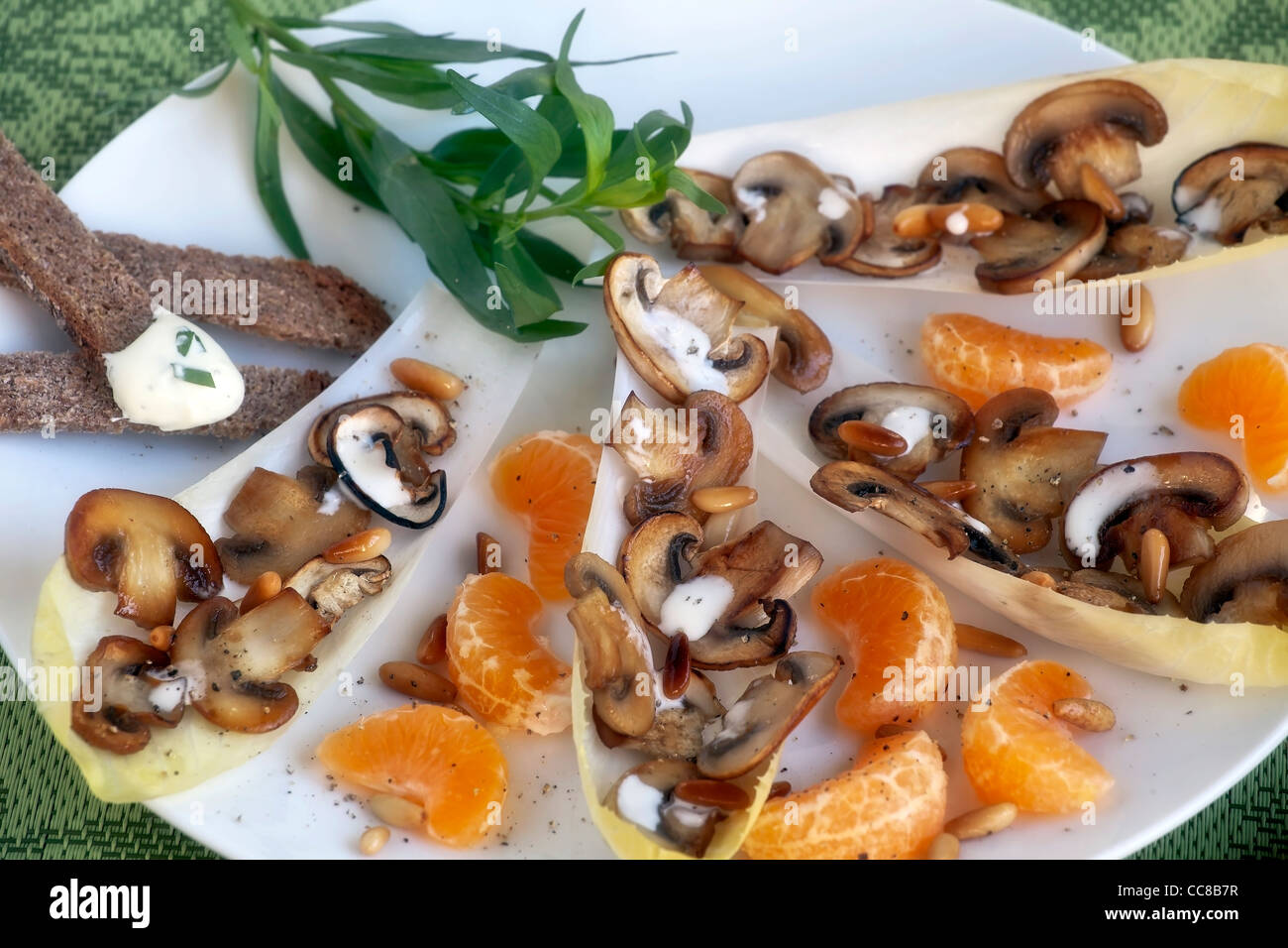 Chicory salad with mandarin oranges, mushrooms and pine nuts  - Stock Image