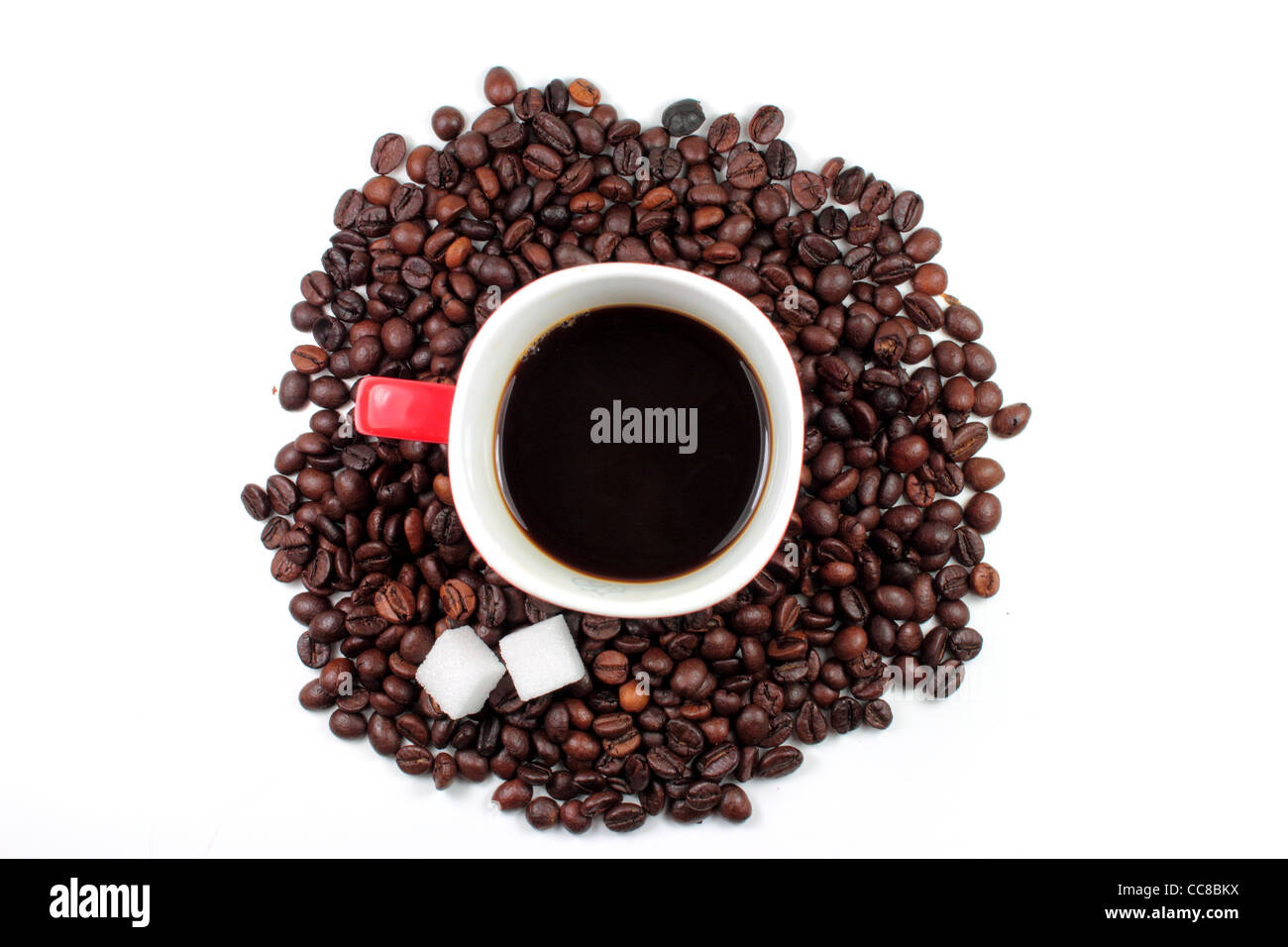 Red mug of coffee with roasted coffee beans and sugar lumps - Stock Image