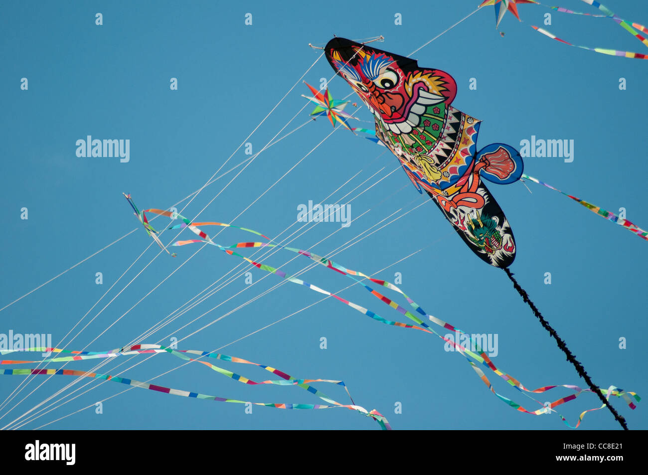 Variety of kites flying against a blue sky - Stock Image