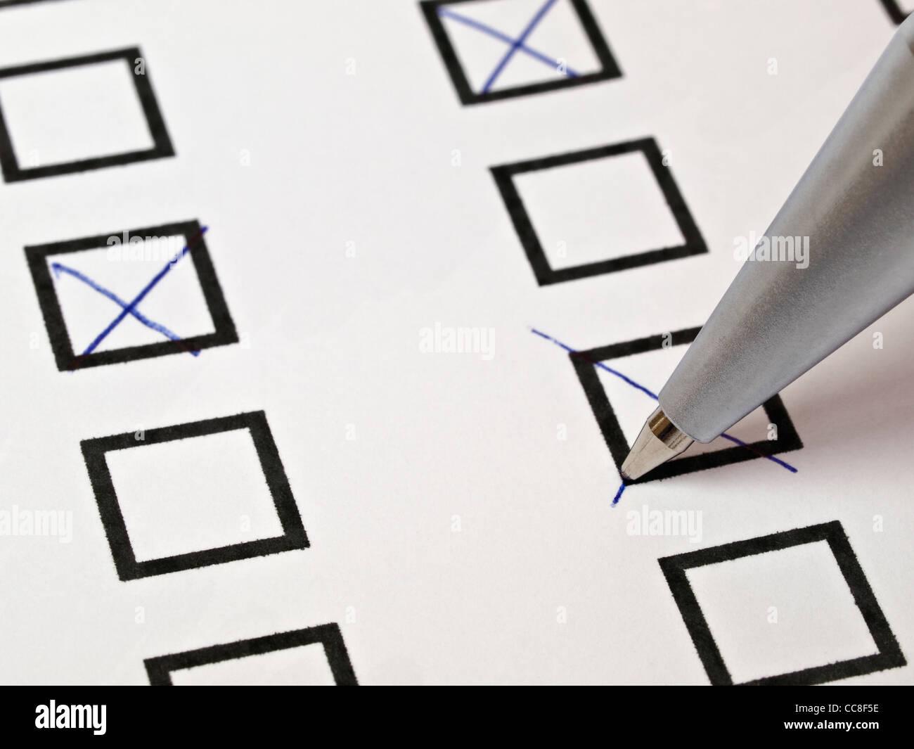 viele Kästchen werden mit einem Kugelschreiber angekreuzt | many small boxes are marked with a cross with a ballpoint Stock Photo