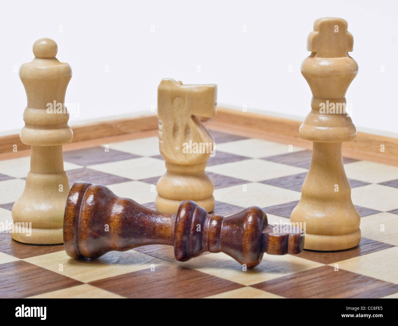 A chessboard, on it is a white queen, a white horse and a white King. In front is the black King topple down. - Stock Image