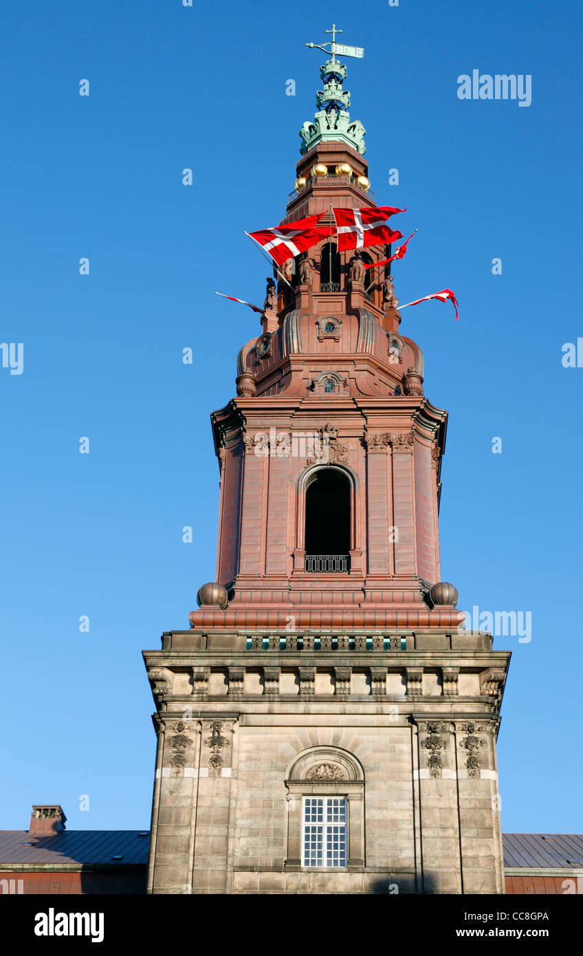 Danish flags in the tower windows of Christiansborg Palace, the parliament building in Copenhagen, Denmark, in celebration. - Stock Image