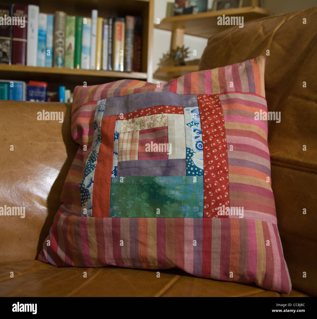 A patchwork cushion on a brown leather armchair - Stock Image
