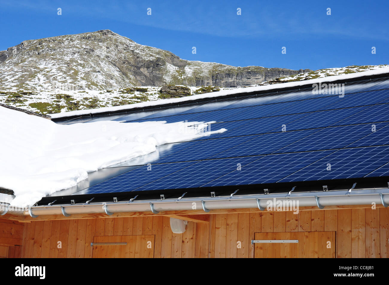 Solar panels on roof of building after snow fall, Switzerland - Stock Image